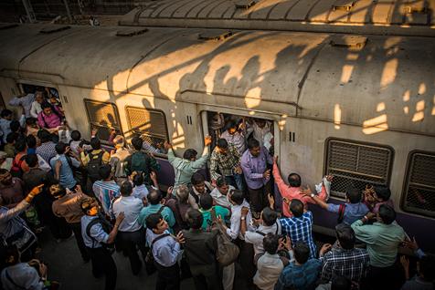 Menschenmassen und Gedränge am Bahnhof in Mumbai: die abendliche Lichtstimmung und der besondere Blickwinkel der Fotografin dominieren die Komposition