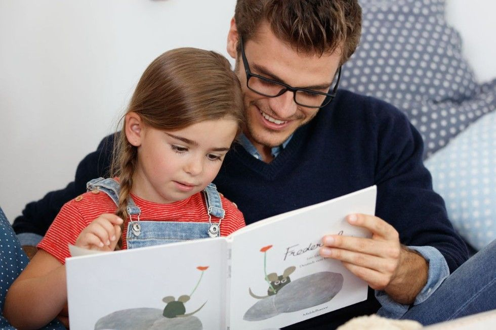 A father reading a story to his little daughter
